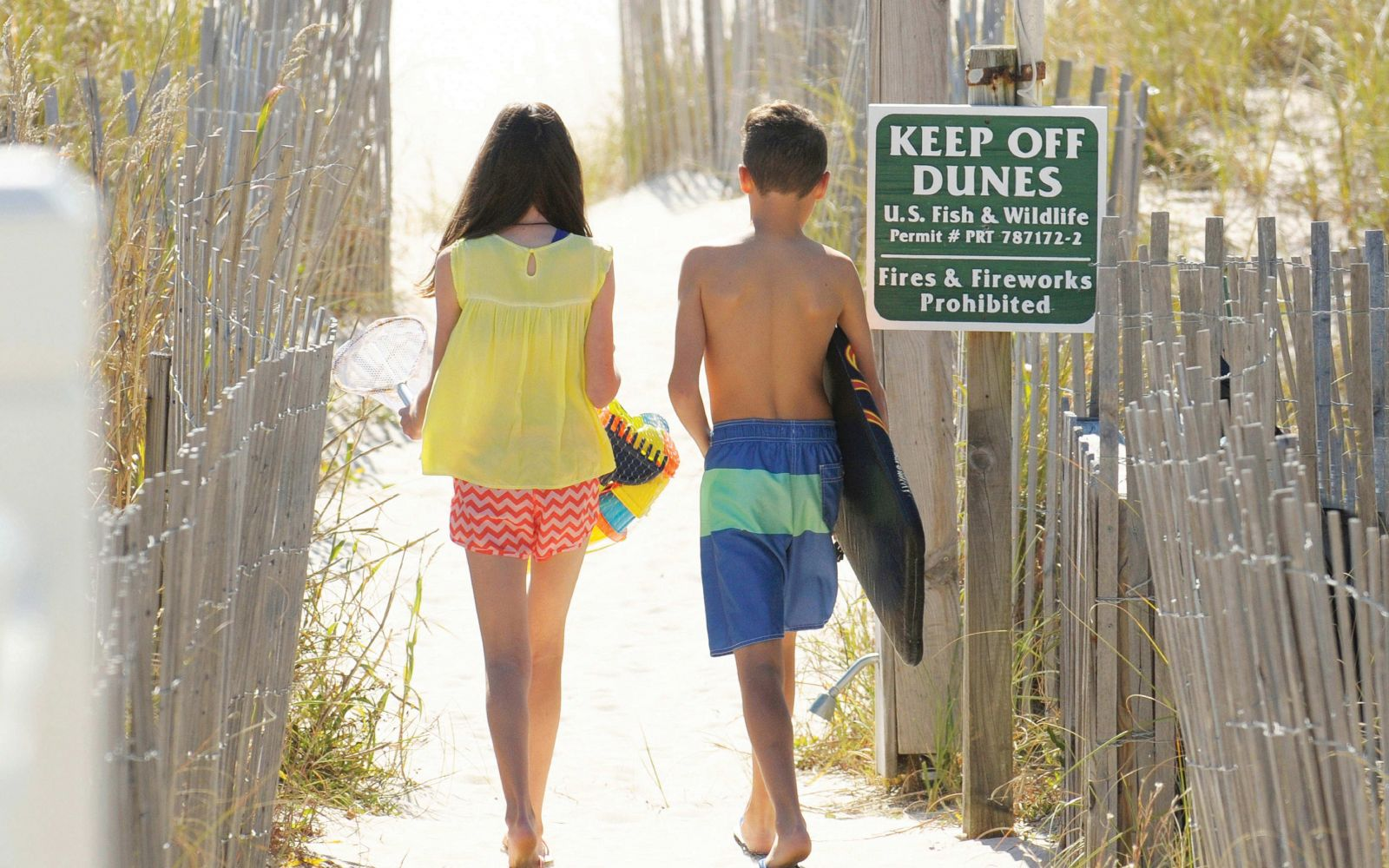 little boy and girl walking to the beach together