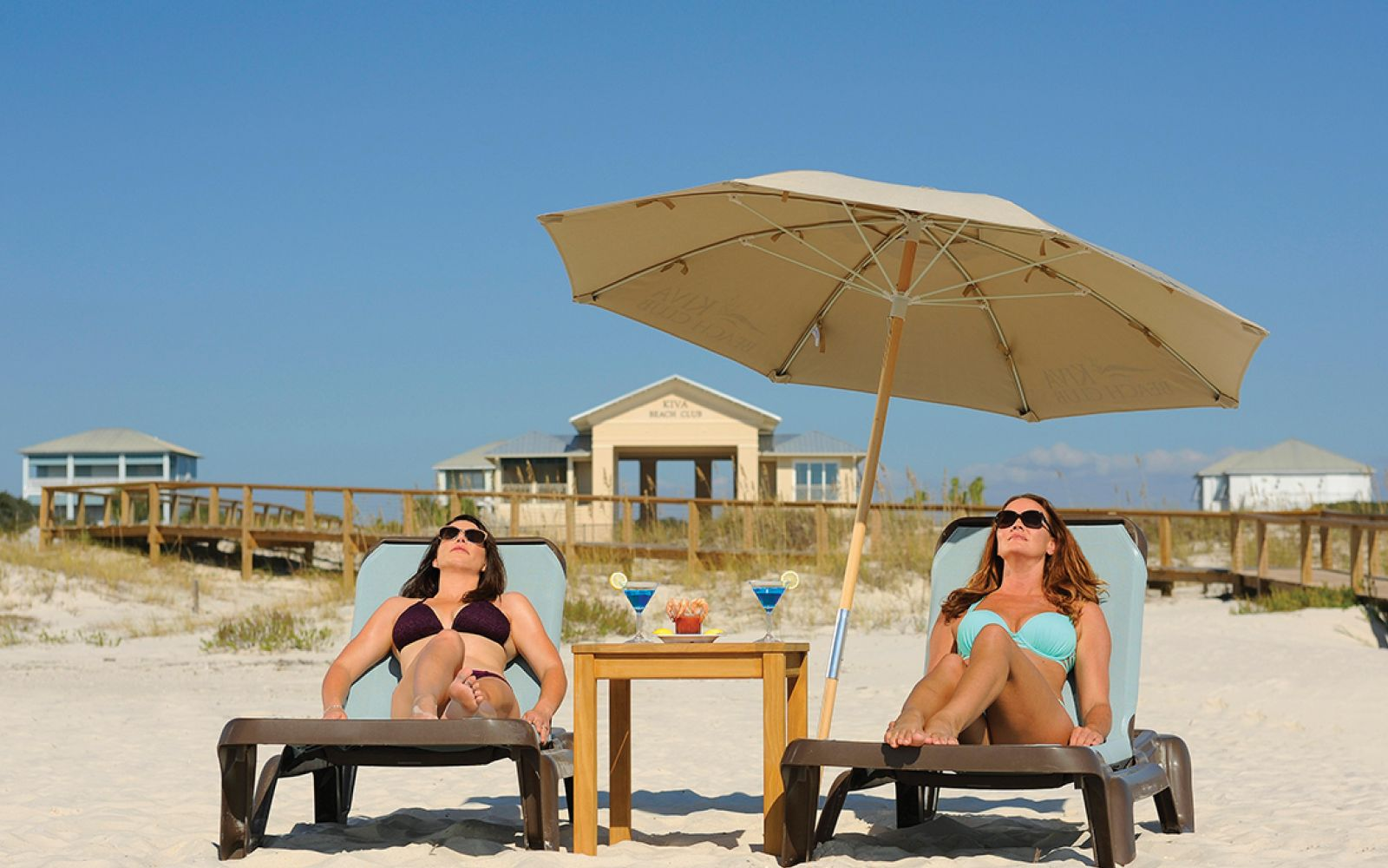 two women laying out on beach loungers underneath umbrella