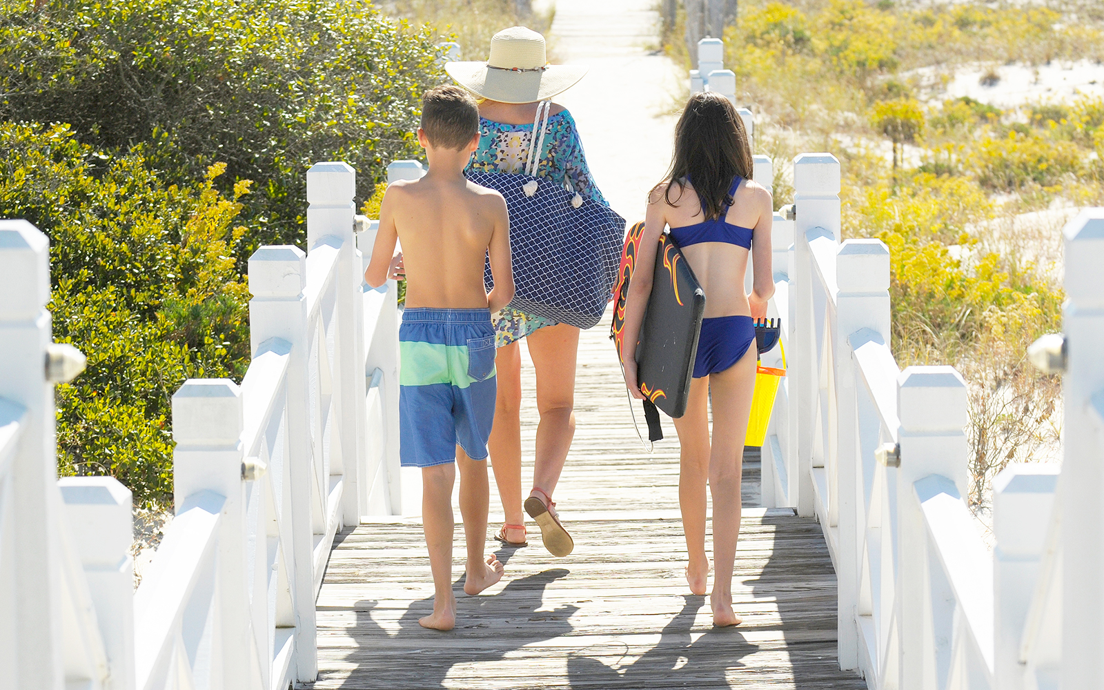 mother with two children walking on the boardwalk towards the beach