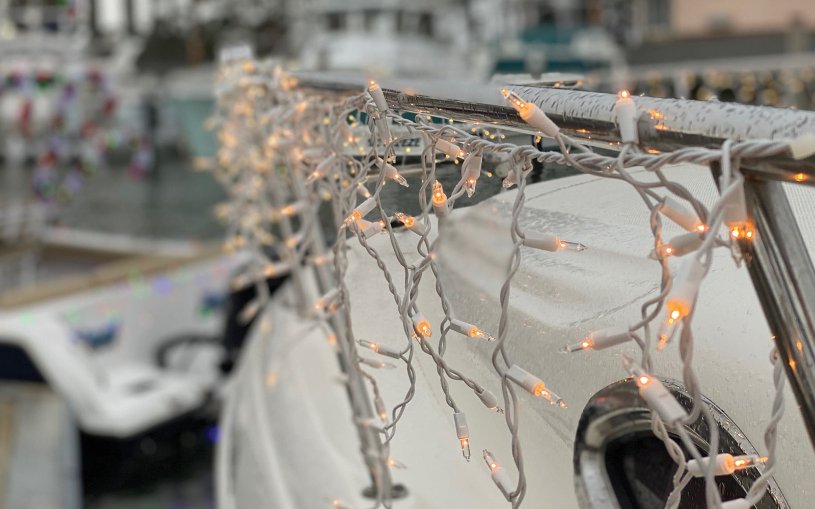 christmas lights hanging from the deck of a boat